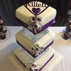 three tier pillared cake white, with purple lillies on one corner, purple ribbon