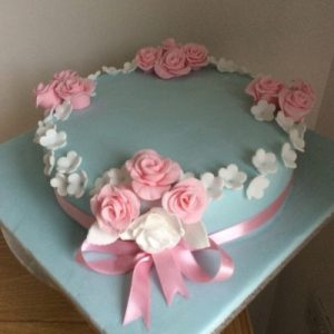 onr teir cake in pastel blue with delicate white and pink roses finished with a pink ribbon