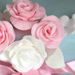 close up of pink and white roses on a baby blue cake