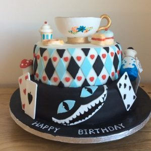 two tier cake Alice in wonder land themed. Bottom teir black with Cheshire cat grin, second tier Harlequin checked and topped with a finely sculpted tea cup and cream tea