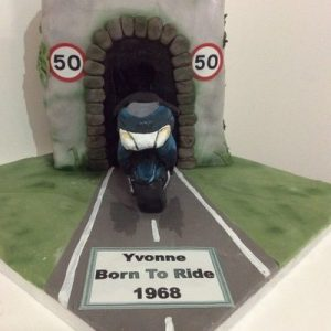 Tunnel effect cake with sculpted chocolate,blue bike coming out of the tunnel, finished with the words Yvonne born to ride