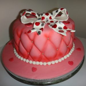Pink quilted look cake with a giant white spotty bow on top