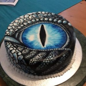 white cake hand painted with a blue dragons eye