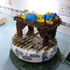 white minion cake decorated like a torture chamber. on top is a chocolate and crispie stretching rack with 3 minions stretched and various whips and implements, bottom view