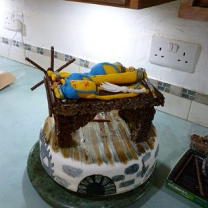 white minion cake decorated like a torture chamber. on top is a chocolate and crispie stretching rack with 3 minions stretched and various whips and implements, side view