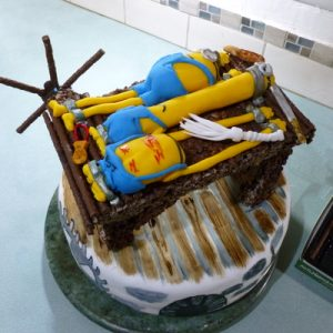 white minion cake decorated like a torture chamber. on top is a chocolate and crispie stretching rack with 3 minions stretched and various whips and implements