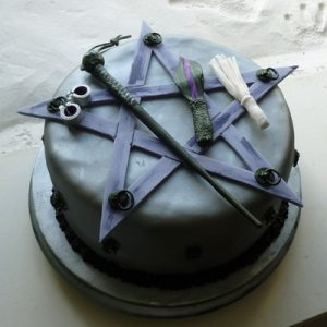 purple cake with 5 pointed star and handcuff and whip details