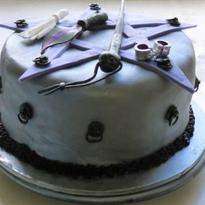purple cake with 5 pointed star and handcuff and whip details, side view