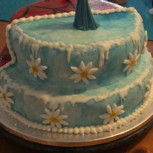 Half spider man,red with silhouette of sky line and half frozen themed cake, blue with icicles and white and yellow daisies, frozen side view