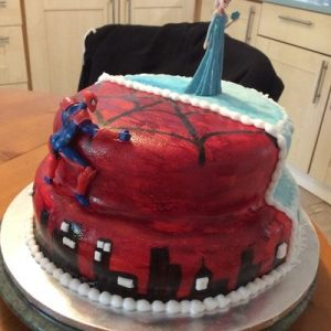 Half spider man,red with silhouette of sky line and half frozen themed cake, blue with icicles and white and yellow daisies spider man side