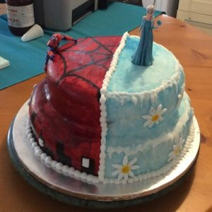 Half spider man,red with silhouette of sky line and half frozen themed cake, blue with icicles and white and yellow daisies