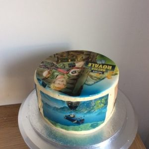 Round cake with hand painted fortnite painted topper and printed themed sides