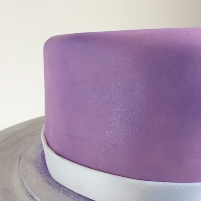 close up of one side of a cake covered in purple icing and a soft purple shimmer dusting