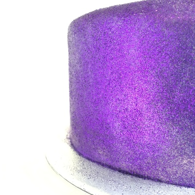 close up of one side of a cake covered in solid purple glitter