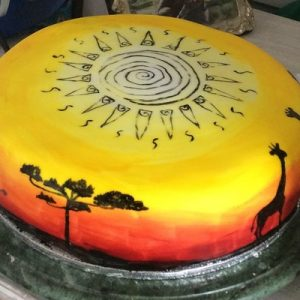 African sunset cake, sunset colours around the edge with African animals and trees in silhouette and sun design on top