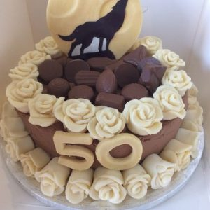 chocolate cake with 2 rows of white chocolate roses, topped with a moon and howling wolf silhouette. Number 50 on front