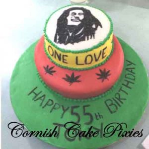 two tier red and yellow cake with hand painted Bob Marley on top and cannabis leaves
