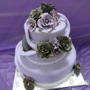3 tier wedding cake in black and purple with purple swags and purple and black gold edged roses purple side