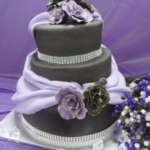 3 tier wedding cake in black and purple with purple swags and purple and black gold edged roses