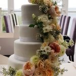 4 tier white wedding cake with fresh flower sweeping down from the top layer