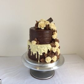 two tier chocolate cake white chocolate drizzle and chocolate roses
