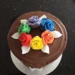 Rainbow cake in chocolate with rainbow roses