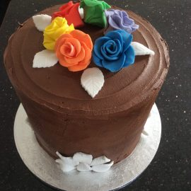 Rainbow cake in chocolate with rainbow roses